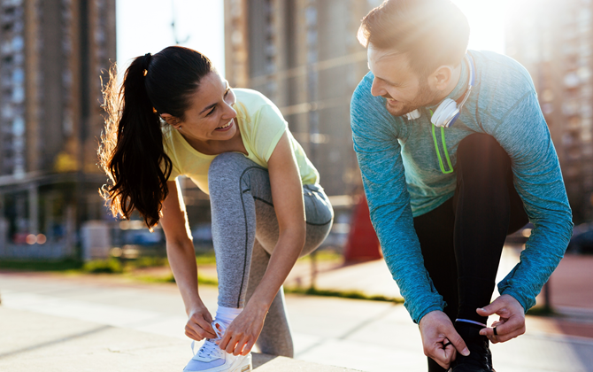 Energetic woman and man smiling and preparing for being active and working out in the city