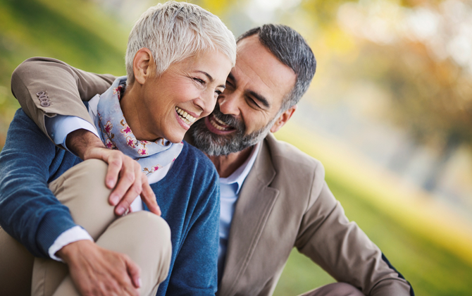 Vibrant looking, smiling middle aged couple hugging in the park